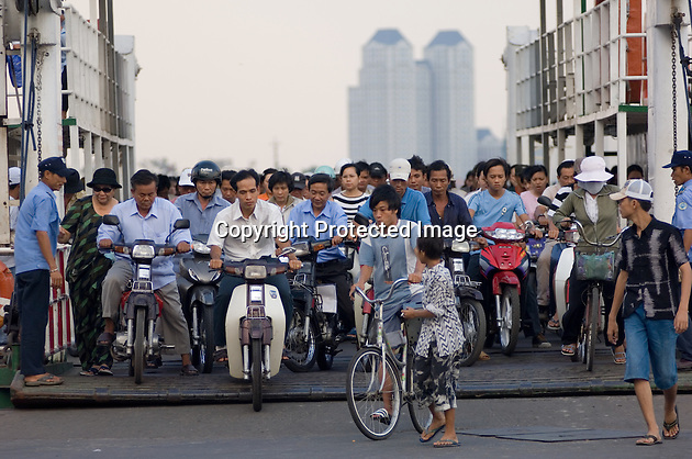 Passengers on mopeds and bicyles, as well as some on foot, pour off a cross-river ferry in Saigon (Ho Chi Minh City), Vietnam.