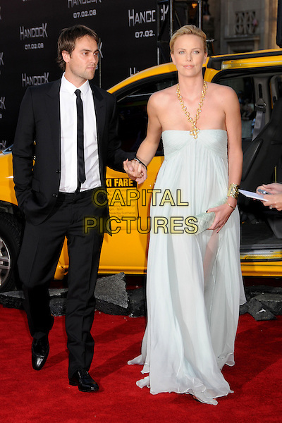 "STUART TOWNSEND & CHARLIZE THERON.""Hancock"" Los Angeles Premiere at Grauman's Chinese Theatre, Hollywood, California, USA..June 30th, 2008.full length black tie suit white shirt pale blue strapless dress gold necklace clutch bag couple holding hands .CAP/ADM/BP.©Byron Purvis/AdMedia/Capital Pictures."