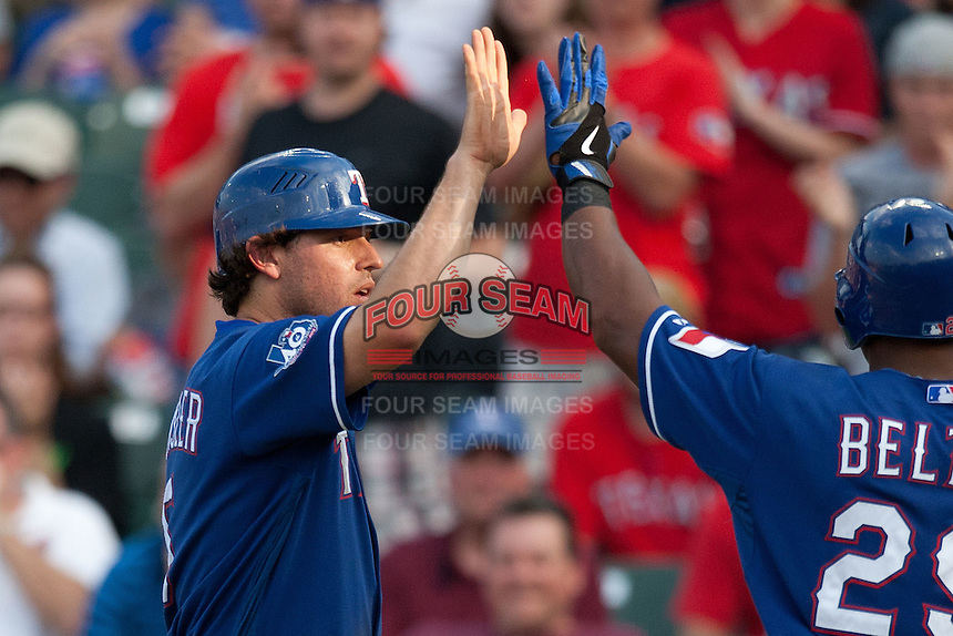 """Texas Rangers second baseman Ian Kinsler #5 greets teammate Adrian Beltre #29 following his home run in the first inning of the MLB exhibition baseball game against the """"AAA"""" Round Rock Express on April 2, 2012 at the Dell Diamond in Round Rock, Texas. The Rangers out-slugged the Express 10-8. (Andrew Woolley / Four Seam Images)."""