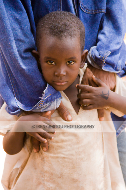 A young Fulani boy holds onto his uncle's hands in Ouagadougou, Burkina Faso.