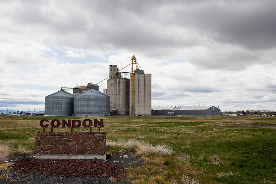 Grain elevators and storage silos are seen behind the town sign in Condon, Oregon located in Gilliam County.