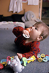 Berkeley CA Unisex baby c. ten-months-old mouthing rattle at daycare
