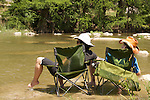 relaxing in the river on a campout while their kids play in the water