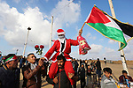 A Palestinian man dressed up as Santa Claus gives artificial flowers to Palestinian protesters during clashes with Israeli troops in tents protest where Palestinians demand the right to return to their homeland at the Israel-Gaza border, in Khan Younis in the southern Gaza Strip on December 21, 2018. Photo by Ashraf Amra