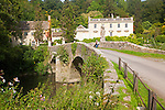 Bridge crossing the River Frome and the classical Georgian facade of Iford Manor, near Freshford, Wiltshire, England