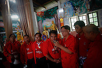 Local red shirt leaders gather around a mobile phone to talk to ousted premier Thaksin Shinawatra during a religious ceremony at a temple in the village of Suan Mon near Udon Thani in northeastern Thailand June 25, 2011. Saffron-robed monks chanted and young women in silk sarongs stretched out their arms in traditional Thai dance moves, but the big event was the voice on a scratchy telephone line from another continent. ?Be prepared. Good things are about to come,? billionaire former prime minister Thaksin Shinawatra said from his Dubai mansion in a telephone call to a Buddhist temple where 38 communities declared their allegiance to Thaksin, formally becoming ?Red Shirt Villages? in solidarity with the red-shirted movement that backs him. The red shirts, supporters of ousted premier Thaksin Shinawatra, have been branding hundreds of villages as red to rally behind Thaksin's sister, Yingluck, who is leading the opposition ahead of July 3 general elections. Picture taken June 25, 2011. TO GO WITH THAILAND-ELECTION/THAKSIN REUTERS/Damir Sagolj (THAILAND)