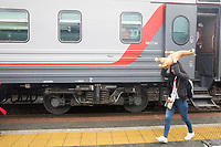 CHELYABINSK, RUSSIA - June 21, 2018: A Peru fans shields herself from rain drops  with an inflatable lama after arriving in Yekaterinburg after a five hour train ride from Chelyabinsk, Russia. They traveled to  Yekaterinburg for their 2018 FIFA World Cup group stage match against France at Yekaterinburg Arena Stadium.