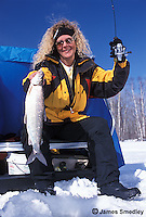 Woman holding whitefish that she caught ice fishing