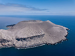San Benedicto Island, Revillagigedos Islands, Mexico;  an aerial view of the cinder cone created in the 1952 volcanic eruption, as viewed from the windward side of the island, with afternoon clouds overhead