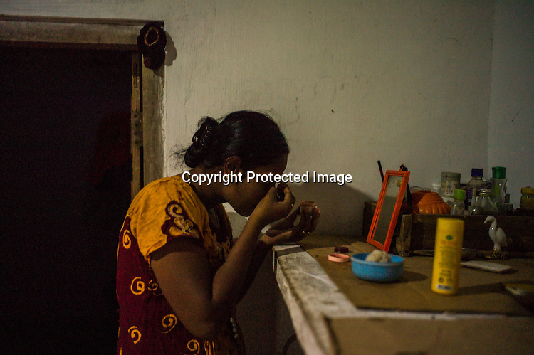 Mathumita puts on the make up after bathing her son at her mother's house in Punaineeravi village in Kilinochchi in Northern Sri Lanka. Photo: Sanjit Das/Panos