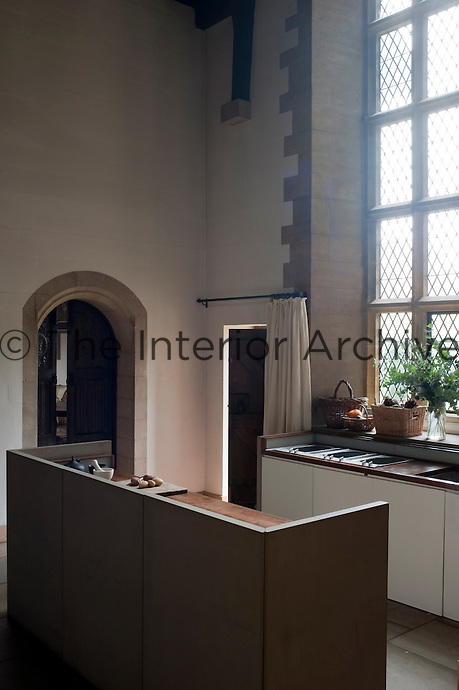 The simple modern free-standing kitchen is located beside the dramatic mullioned windows of the original room
