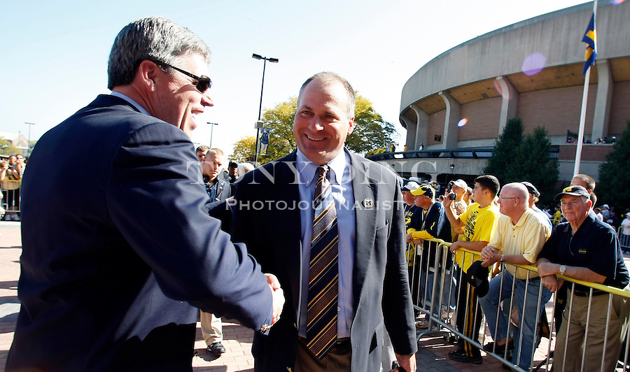 Michigan Athletic Director David Brandon, left, shakes hands with head coach Rich Rodriguez at the entrance to Michigan Stadium before an NCAA college football game with Michigan State, Saturday, Oct. 9, 2010, in Ann Arbor, Mich. (AP Photo/Tony Ding)