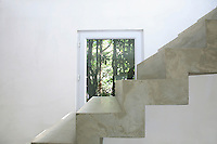 In the living/dining area the concrete staircase has been left untreated and bare for a functionally minimalist feel