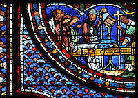 Saint Maximin reads prayers over the body of Mary, the death of Mary Magdalene, from the Life of Mary Magdalene stained glass window, 13th century, in the nave of Chartres cathedral, Eure-et-Loir, France. Chartres cathedral was built 1194-1250 and is a fine example of Gothic architecture. Most of its windows date from 1205-40 although a few earlier 12th century examples are also intact. It was declared a UNESCO World Heritage Site in 1979. Picture by Manuel Cohen