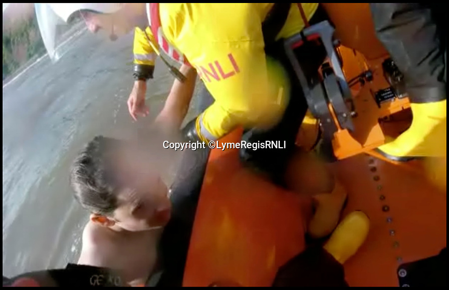 BNPS.co.uk (01202 558833)<br /> Pic : LymeRegisRNLI/BNPS<br /> <br /> The lifeboat crew pull the boys into the boat.<br /> <br /> This is the dramatic moment two teenage tombstoners were saved from drowning after they were swept 250 yards out to sea.<br /> <br /> Archie Woollacott, 14, got dragged away by a strong current after plunging off a harbour wall at Axmouth, Devon. His friend Bozhidrar Bobev jumped in to rescue him but was also taken out to sea.<br /> <br /> The stricken pair spent an hour treading water before they were spotted by the Lyme Regis lifeboat crew in the nick of time.<br /> <br /> The next day Archie visited to RNLI station to thank the crew by baking them a lemon drizzle cake.