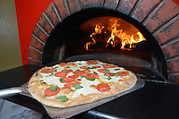 Pizza is placed in a brick oven at Bacco's Bistro Thursday August 13, 2015 in Doylestown, Pennsylvania. (Photo by William Thomas Cain)