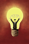 Illustrative image of male representation holding filament in glowing light bulb representing business idea