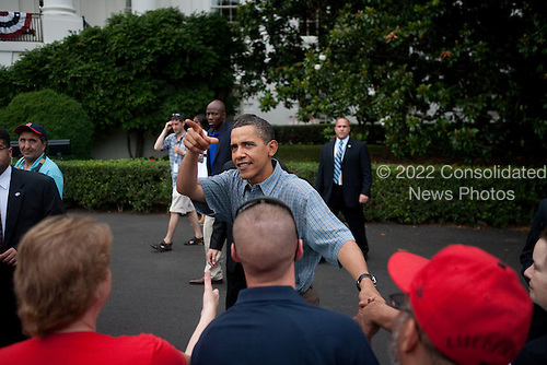 Washington, DC - July 4, 2009 -- United States President Barack Obama points at a photographer while shaking hands with guests at a gathering of military families at the White House on July 4, 2009 in Washington, DC. President Obama is leaving tomorrow on a trip to Russia, Italy, and Ghana. .Credit: Brendan Hoffman - Pool via CNP