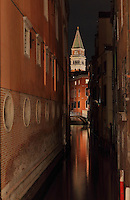 Narrow canal between buildings at night, with view to the St Mark's Campanile or Campanile di San Marco, the bell tower of the basilica, built 1541, Venice, Italy. The city of Venice is an archipelago of 117 small islands separated by canals and linked by bridges, in the Venetian Lagoon. The historical centre of Venice is listed as a UNESCO World Heritage Site. Picture by Manuel Cohen