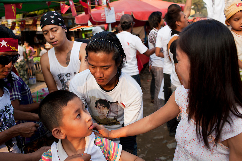 A young National League for Democracy supporter tries on a t-shirt with a photo of Daw Aung San Suu Kyi on it, at a temporary market that was set up to sell NLD merchandise in Mingalar Taung Nyunt township, in Yangon, Myanmar, March 23, 2012.