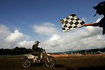 Riders finish on the course with the checkered flag at the Unadilla Valley Sports Center in New Berlin, New York on July 16, 2006, during the AMA Toyota Motocross Championship.