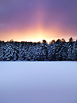 Glowing red sunset behind snow covered trees and a frozen lake. Atmospheric landscape wintertime nature scenery at Algonquin Provincial Park, Ontario, Canada