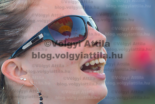 A Balloon is reflected on the sunglasses of a viewer during the Velence Lake International Hot Air Balloon Festival in Agard, Slovakia on September 10, 2011. ATTILA VOLGYI