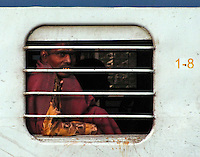 A working man wearing a gold print shirt and wrapped in a dark red blanket looks out the barred, glassless window of the light blue train car 1-8 on a commuter train destined for Khajuarhro from the Agra train station.
