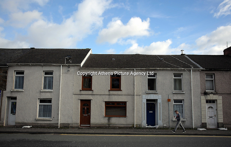 Pictured: A boy walks past terraced houses in Bridge Street in Llangennech, west Wales. Thursday 24 February 2017<br />Re: Plans to convert Llangennech Junior School, a bilingual school to one teaching only welsh, has caused a bitter row between campaigners and politicians in Carmarthenshire, Wales, UK.