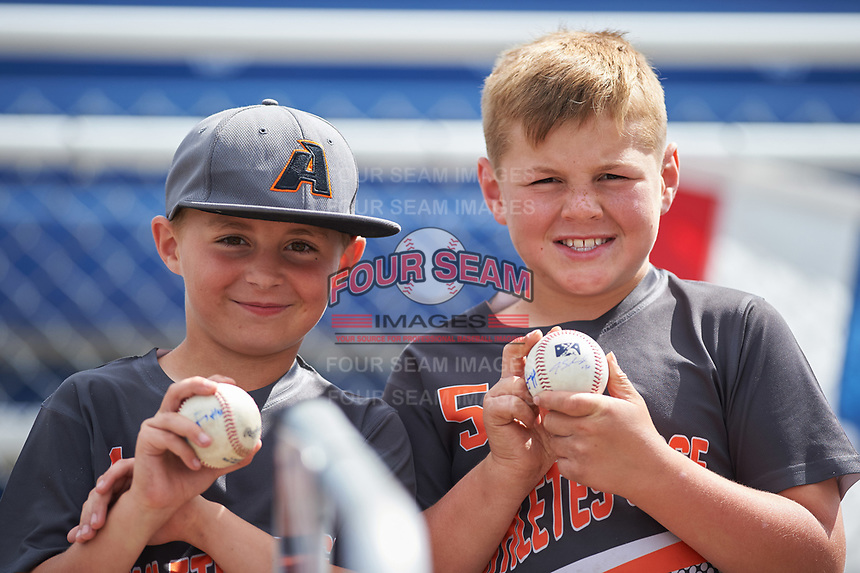 Two young Batavia Muckdogs fans hold up their baseballs before a game against the West Virginia Black Bears on June 25, 2017 at Dwyer Stadium in Batavia, New York.  Batavia defeated West Virginia 4-1 in nine innings of a scheduled seven inning game.  (Mike Janes/Four Seam Images)