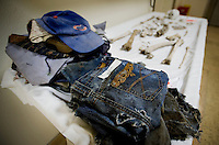 Clothing and bones of a presumed border crosser discovered by a woman riding her horse in the Avra Valley area near Tucson, AZ on June 24, 2009 are displayed on an examination table at the Pima County Medical Examiners office in Tucson, Arizona, Wednesday, August 5, 2009. The medical examination office in Pima County works with the highest number of border crosser deaths along the border. The forensic examination as well as the anthropological exams are the primary steps in making an identification...PHOTOS/ MATT NAGER
