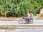 An i-Kiribati couple on a motorcycle on the remote island of Kiritimati in Kiribati.