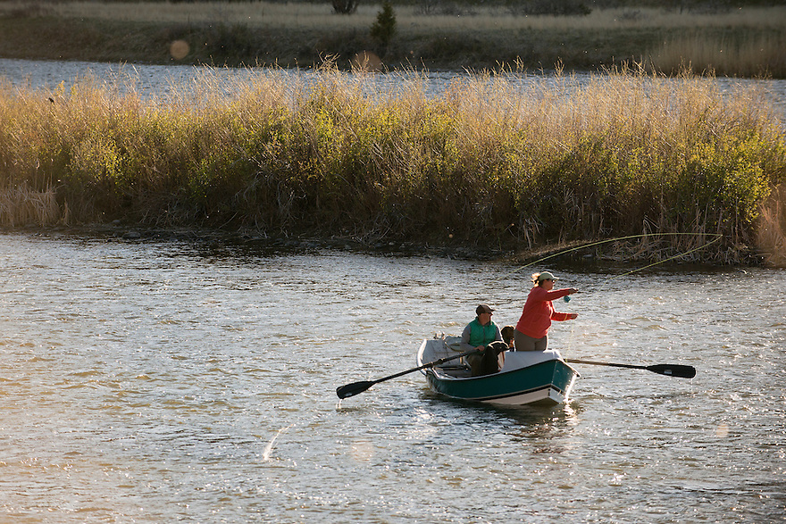 An angler casts from the bow of a drift boat while fishing the Mother's Day caddis hatch on the Madison River near Black's Ford on Monday evening.