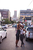 MABONENG, SOUTH AFRICA - MARCH 20: Women take a selfie on the street in Maboneng district on March 20, 2016 in downtown Johannesburg, South Africa. A former derelict industrial area, and a no-go area after dark, it is now a vibrant area with artists, businesses, galleries and tourists. A racially mixed cultural hub with markets on the weekend. Maboneng is the idea of young entrepreneur Jonathan Liebmann, and he owns and controls most of the buildings in the area. (Photo by Per-Anders Pettersson/Getty Images)