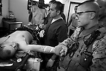A first sergeant holds the hand of one his Marines as medics in the emergency room at Charlie Medical Co. prepare him for surgery to begin repairs of a badly broken leg following  an IED strike in Ramadi, Iraq on Fri. Oct. 06, 2006.