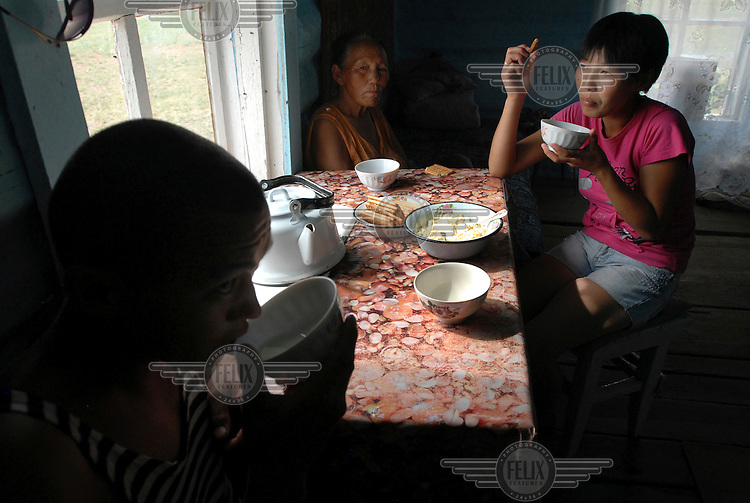 A family have a meal in their house on their goat farm on the outskirts of Kyzyl.