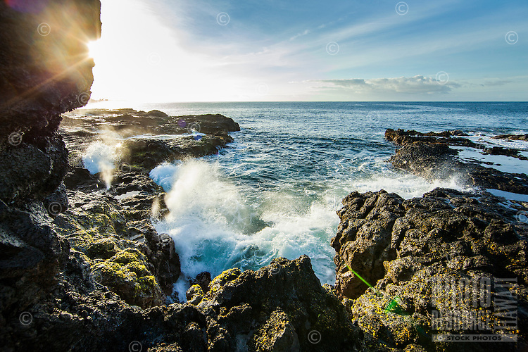Waves crash up against lava rocks in the morning on Kaua'i.