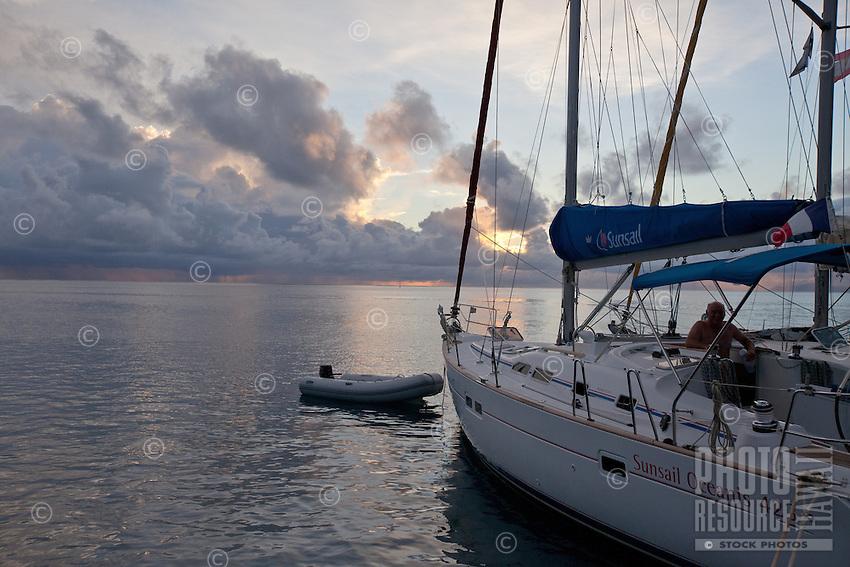 Man on cruising yacht at sunrise