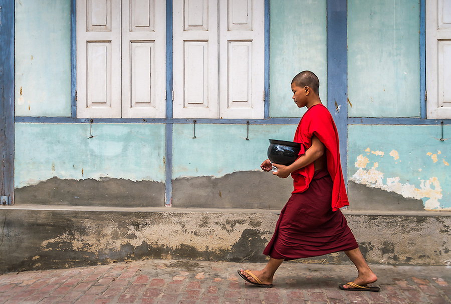 MANDALAY, MYANMAR - CIRCA DECEMBER 2013: Monk walking and carrying bowl with lunch in the Mahar Gandar Yone monastery in Amarpura