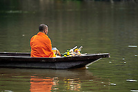 A monk goes for an alms-round on the Ping River in Chiang Mai, Thailand. Everyday from dawn until around 7:00 a.m., monks in Thailand walk, or float, with alms bowls in the area around their monastery. The act of giving alms is a common practice among Thai Buddhists and a symbolic connection to the spiritual that shows humbleness and respect.