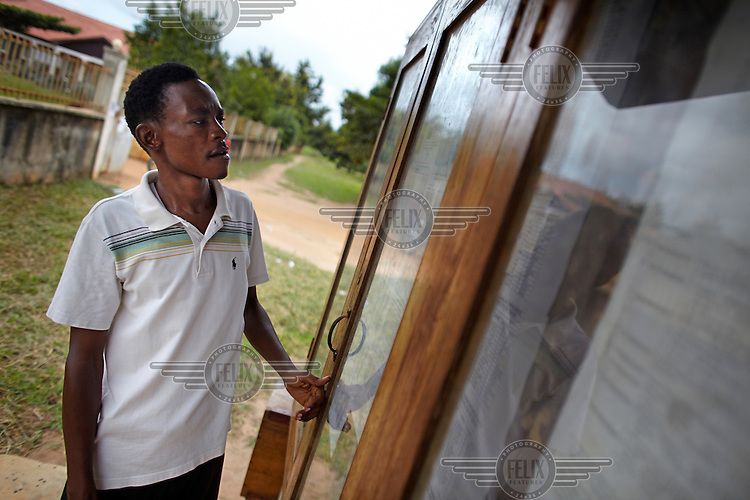 Arafat Hamis checks a 'transparency board' outside government offices in Tandahimba. Such boards are a link between the government and the local community providing important information on government revenues and expenditure in the area.