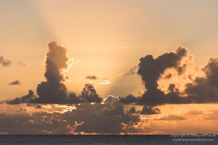 Toau Atoll, Tuamotu Archipelago, French Polynesia; the sun setting on the horizon sends rays of light up from behind the clouds