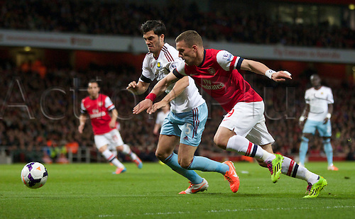 15.04.2014.  London, England. Lukas Podolski of Arsenal (right) chases down the ball with James Tomkins of West Ham United in close attendance during the Barclays Premier League match between Arsenal and West Ham from the Emirates Stadium.