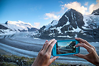 Hands on a phone making images of the Grand Combin and Glacier de Corbassière at sunset, Val de Bagnes, Switzerland