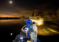 Guide Ron Russell, Gator Getter Consutants, left, shines a light along the bank of the Cooper River looking for alligators as hunter Jeff Bannister, of Greenville, watches during an alligator hunt Oct. 5, 2008 in Moncks Corner, South Carolina. After 40 years, the Department of Natural Resources (DNR) issued 1,000 permits to hunt alligators in South Carolina in an effort to control the population which numbers more than 100,000. (Paul Zoeller/pressphotointl.com)