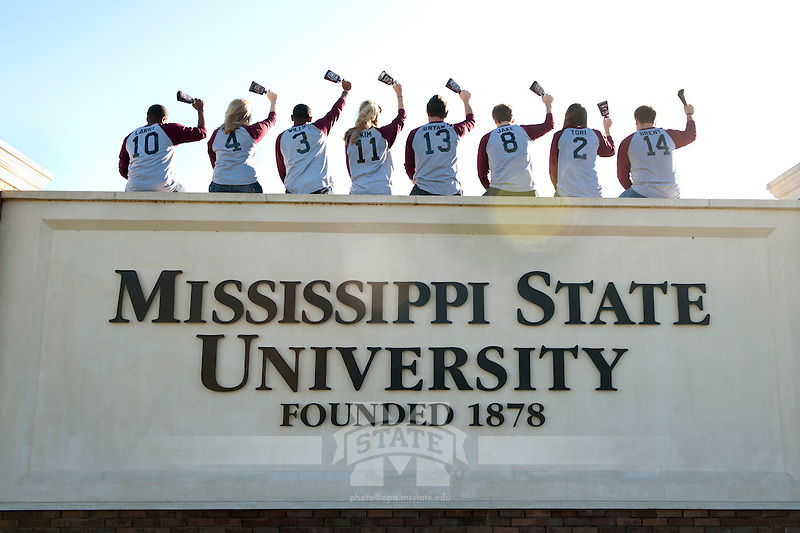 Students perched on the entrance sign ringing cowbells. (photo by Beth Wynn / © Mississippi State University)