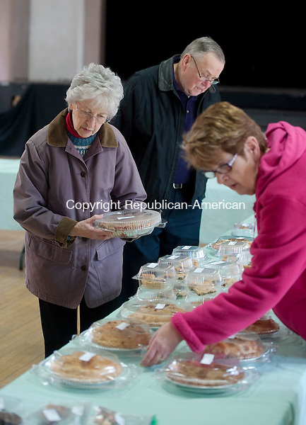 NAUGATUCK, CT--- -021916JS05- Church volunteer Gloria DelPrincipe, right, helps customers Jill and Richard Haines of Waterbury, left,  as they shop during the Saint Michael's Lenten Bakery held Friday at the Saint Michael's Episcopal Church's Paris Hall in Naugatuck. The bakery is open every Friday from noon to 4 p.,. thought March 18th. All of the baked goods are made by volunteers. The Haines' picked up an apple pie during their visit. <br />   Jim Shannon Republican-American