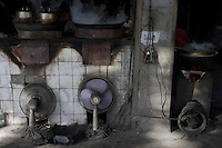Electric fans are used to inflame coal burning stoves at local food stall in Nanjing, Jiangsu province, China, November 2012.