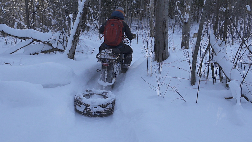 VIDEO FRAME GRAB--Tyler Gauthier of the Range Area Mountain Bike Association of Marquette County Michigan grooms winter singletrack trails with a Rokon motorcycle.