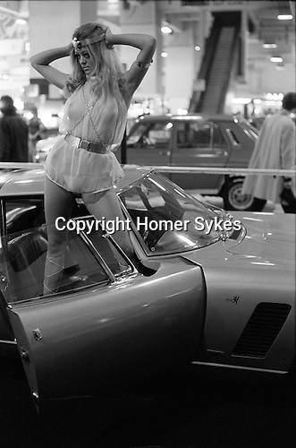Earls Court Motor Show . Promotion girl in costume selling cars with sex appeal. Model wears see through blouse. London England. 1971 Selling cars with sex.